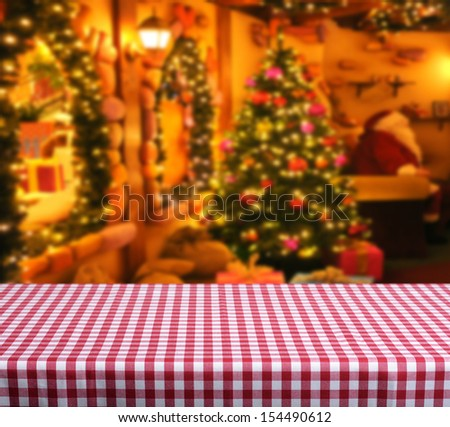 Empty wooden table for product display montages. Santa claus home in background - stock photo