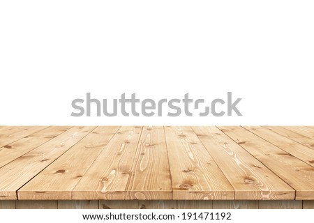 Empty wooden table in a sun drenched summer garden for product placement or montage with focus to the table top in the foreground, with white background. - stock photo