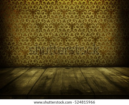 Empty wooden table over grunge gold ornamental wallpaper for product montage and presentation. Dark interior template