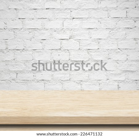Empty wooden table over white brick wall, template - stock photo