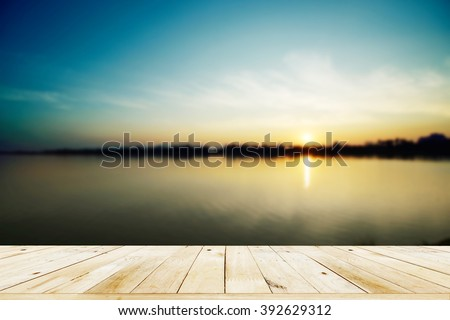 Empty wooden table with sunset on the river blur background.
