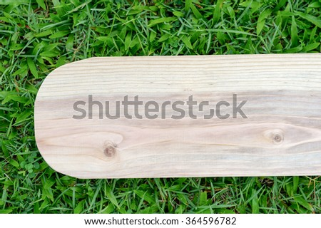 Empty wooden texture on blurred grass background ready for product display montage.