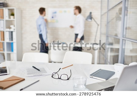 Empty workplace in office with businessmen interacting on background  - stock photo