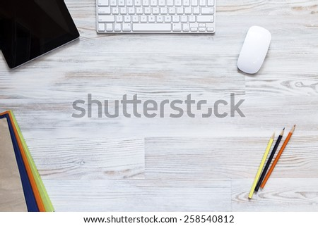 Empty workspace on wooden table. View from above on the clean, well organized working space framed by tablet PC, keyboard, mouse, colored booklets and pencils. - stock photo