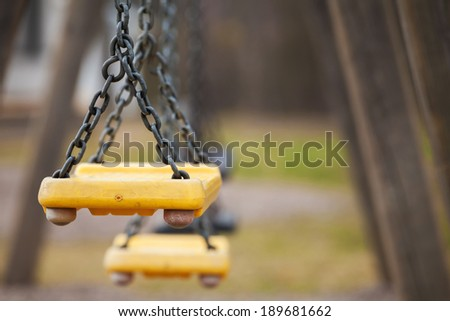 Empty yellow plastic swings on playground - stock photo