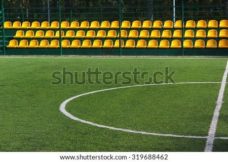 Empty yellow seats at mini soccer stadium - stock photo