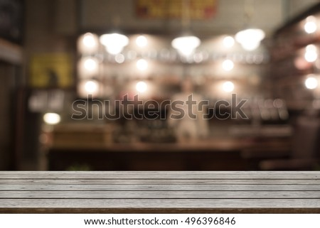 Emthy wood top table with space for display product, montage, with vintage blur or defocus image of cafe or coffee shop background
