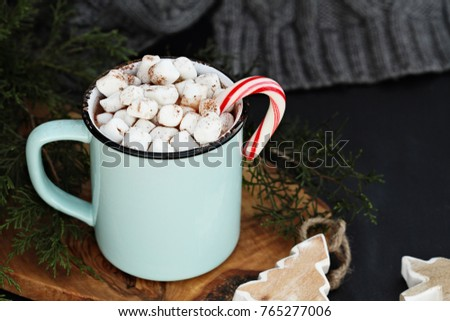 Enamel cup of hot cocoa drink with marshmallows and candy cane against a rustic background with beautiful wood Christmas tree ornaments and a grey scarf. Perfect winter time treat.