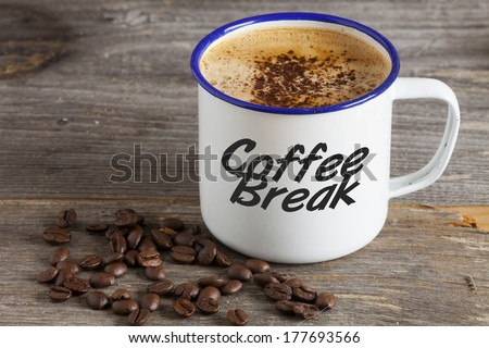 "Enamel Mugs with hot Coffee and Coffee Beans on a rustic wooden board with the Word ""Coffee Break"" on the Cup"