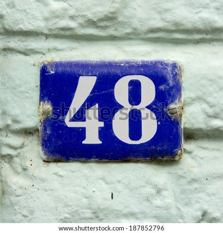enameled house number forty eight. White lettering on a blue background. - stock photo