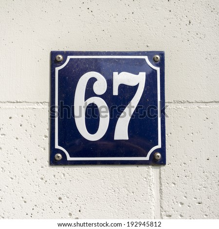 enameled house number on a wall of natural stone - stock photo