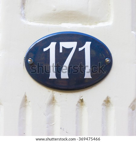 Enameled house number one hundred and seventy one. White numerals on a blue oval background. - stock photo