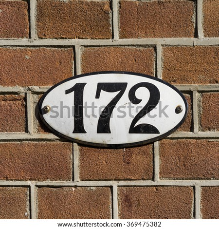 enameled house number one hundred and seventy two on an oval plate. - stock photo
