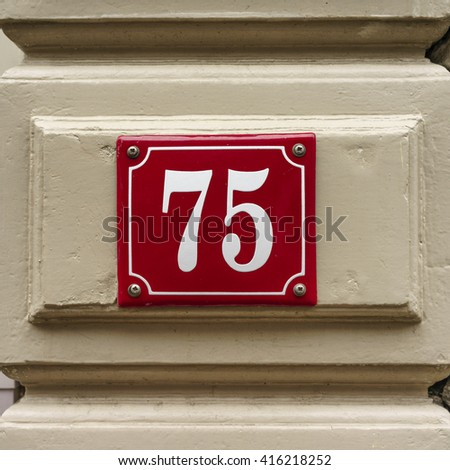 Enameled house number seventy five - stock photo