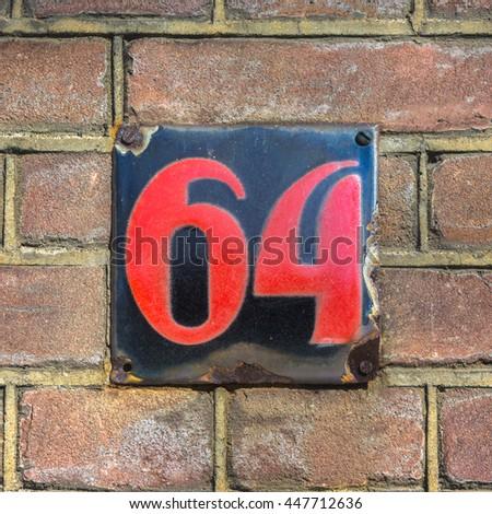 Enameled house number sixty four - stock photo