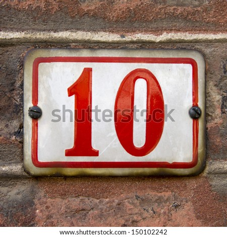 enameled house number ten. Red lettering on a white background. - stock photo