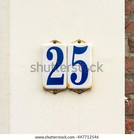 Enameled house number twenty five. - stock photo