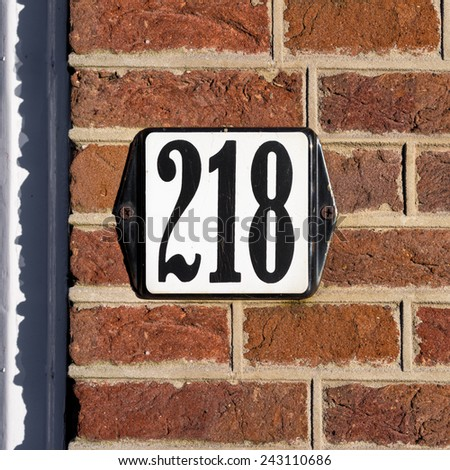 Enameled house number two hundred and eighteen - stock photo
