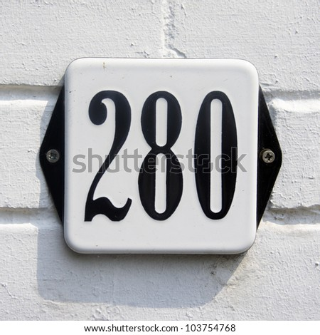 enameled house number two hundred and eighty. Black lettering on a white plate.