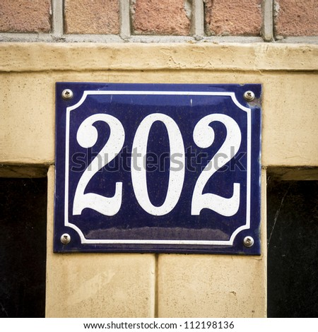 Enameled house number two hundred and two. White lettering on a blue background - stock photo