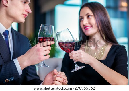 Enamored a gala dinner for two. Romantic dinner in the restaurant. Young loving couple visits a restaurant and raised their glasses of wine close-up view - stock photo