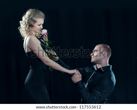 enamored man gives a rose to girl - stock photo