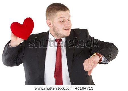 Enamoured guy with a toy in the form of heart looks at the watch. Isolated over white. - stock photo