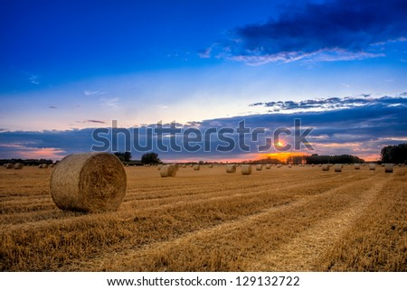 End of day over field with hay bale in Hungary- This photo make HDR - stock photo