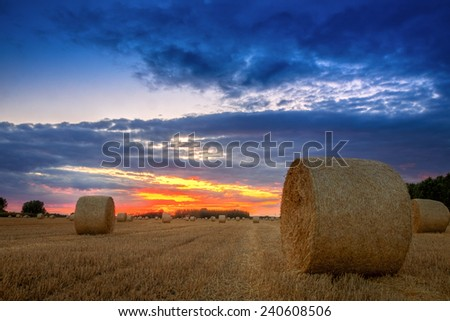 End of day over field with hay bale in Hungary. This photo make in HDR technic - stock photo