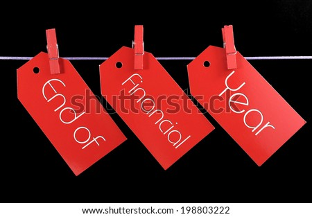End of Financial Year red ticket sale tags hanging from pegs on a line against a black background. - stock photo
