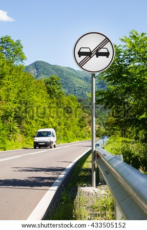 End of overtaking prohibition road traffic sign on a signpost at the side of a mountainous road with an approaching white car - stock photo