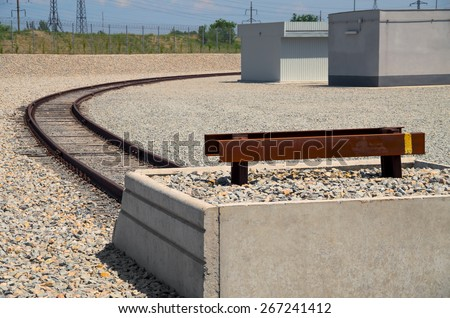 End of rail in an industrial area on background of gravelly embankment and utility poles. - stock photo