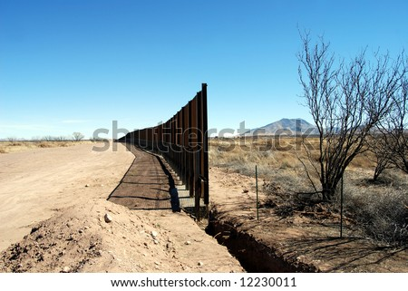 End of U.S.-Mexico border fence under construction in Arizona desert (U.S. to the left, Mexico to the right) - stock photo