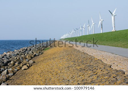 Endless dike with windmills in the Netherlands - stock photo