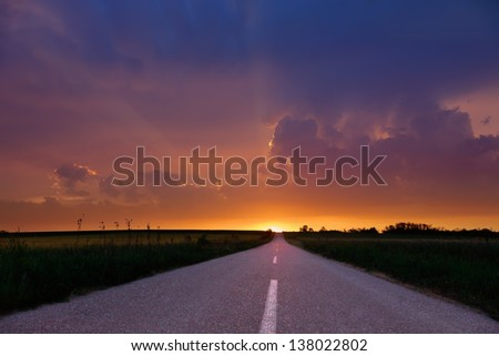 Endless driving on country road at sunset. - stock photo