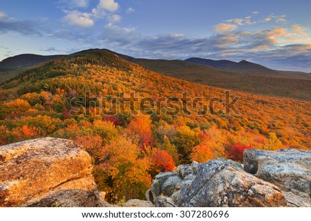 Endless forests with fall foliage in the White Mountain National Forest, New Hampshire, USA. Photographed from North Sugarloaf at sunset. - stock photo