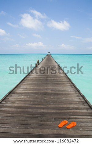 endless jetty to the horizon; view to a turquoise sea and blue sky with white clouds - stock photo