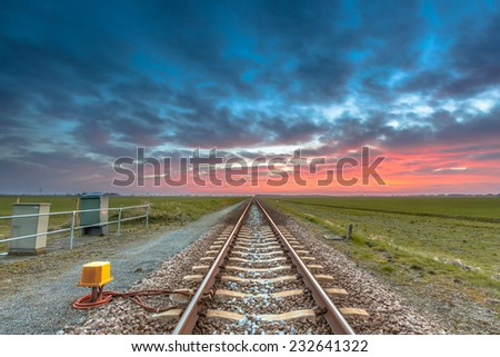 Endless railroad to the horizon under a blue and red sky as a concept for future career. - stock photo