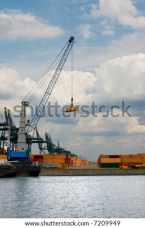 Endless row of large containers waiting beside the cranes in one of the docks of Antwerp world harbor (every single brand name or logo has been removed) - stock photo