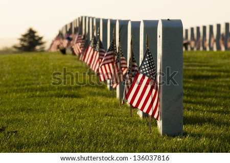 Endless row of white marble gravestones continues above hilltop at the Fort Logan National Cemetery in Denver, Colorado. American flags decorating each grave to mark the Memorial Day. - stock photo