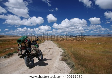 Enduro motorcycle traveler with suitcases standing on a dirt road vanishing into the skyline under a blue sky with white clouds, Plateau Ukok, Altai mountains, Siberia, Russia. - stock photo