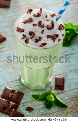 Energetic charge from tasty milkshake for all day. Rich for calories drink with ice cream, whipped topping, kiwi, mint and chocolate on the blue old table. - stock photo