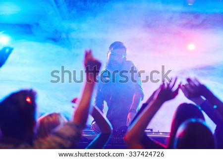 Energetic deejay and dancing crowd enjoying disco in night club - stock photo