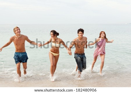 Energetic group of four friends laughing running together on the shore of a white sand beach on holiday, joyfully having fun and enjoying an exciting trip. Travel and teenagers lifestyle. - stock photo