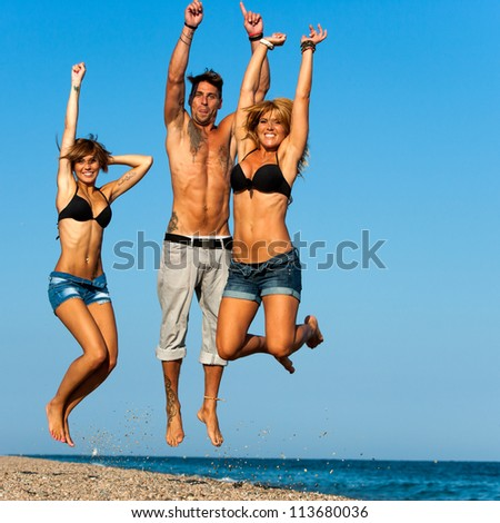 Energetic group of young friends jumping on beach.