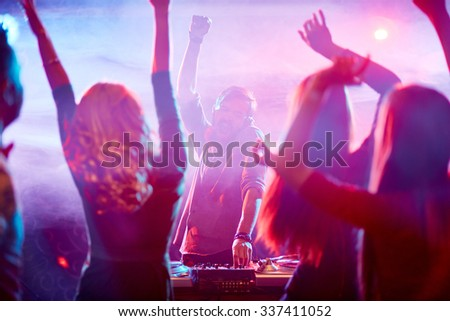 Energetic people dancing in front of ecstatic dj