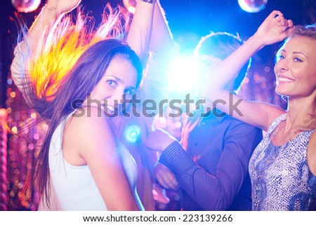 Energetic young people dancing in night club  - stock photo