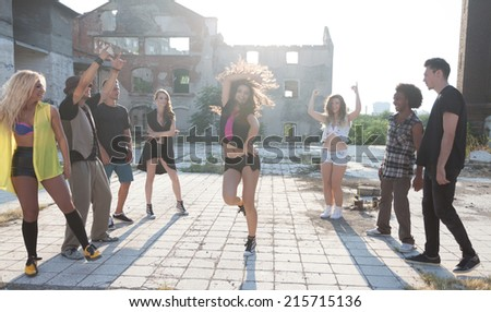 Energetic young people hip hop street dancers performing their routine in an urban square backlit by a bright sun flare over high-rise buildings