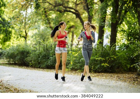 Energetic young women running outdoors in park to keep their bodies in shape - stock photo