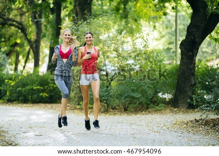 Energetic young women running outdoors in park to keep their bodies in shape